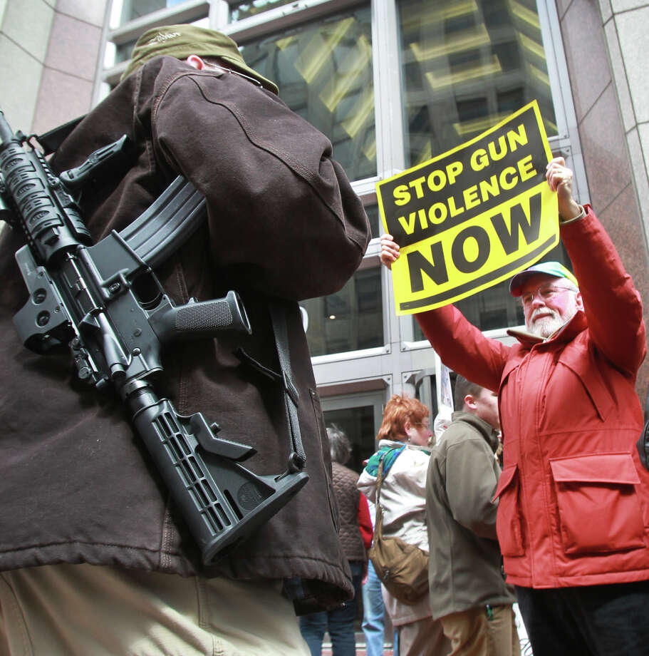 Gun-control advocates face  off against gun rights supporters during a recent gun-control rally in Indianapolis. One solution may be requiring gun owners to obtain liability insurance, a readers suggests. Photo: Charlie Nye, Associated Press / The Indianapolis Star