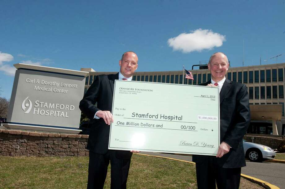 OdysseyRe President and CEO Brian D. Young, left, presents a $1 million check to Stamford Hospital President and CEO Brian G. Grissler of New Canaan for the construction of a new building. Photo: Contributed