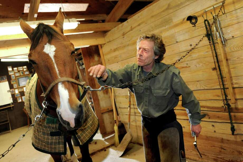 Farrier Jim Santore talks with Cedar, a schooling horse, while shoeing him on Tuesday, April 9, 2013, at Van Lennep Riding Center in Saratoga Springs , N.Y. (Cindy Schultz / Times Union) Photo: Cindy Schultz, Albany Times Union / 10021904A