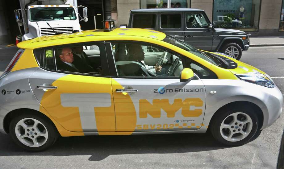 New York Mayor Michael Bloomberg, left, arrives in an electric taxicab for a press conference on Monday, April 22, 2013 in New York.  Six Nissan-donated Leaf all-electric vehicles will be part of a city pilot program to see how their charging dynamic will fit into the typical 24/7 day-to-day taxi operation. Photo: Bebeto Matthews, AP / AP