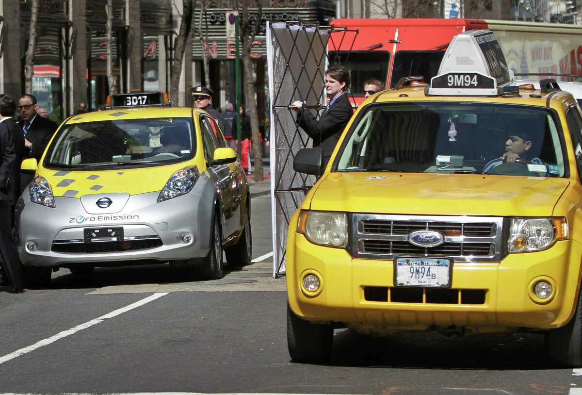 An electric taxicab, left, draws stares at a press conference on Monday, April 22, 2013 in New York. Mayor Michael Bloomberg announced that six Nissan-donated Leaf all-electric vehicles will be part of a city pilot program to see how their charging dynamic will fit into the typical 24/7 day-to-day taxi operation.