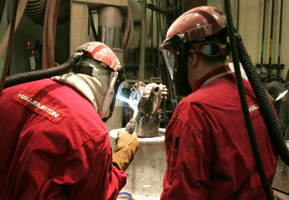 Employees of Security DBS Drill Bits, a unit of oil industry services provider Halliburton Co, work at brazing a drill bit at The Woodlands, Texas facility. Photo: Pat Sullivan, AP