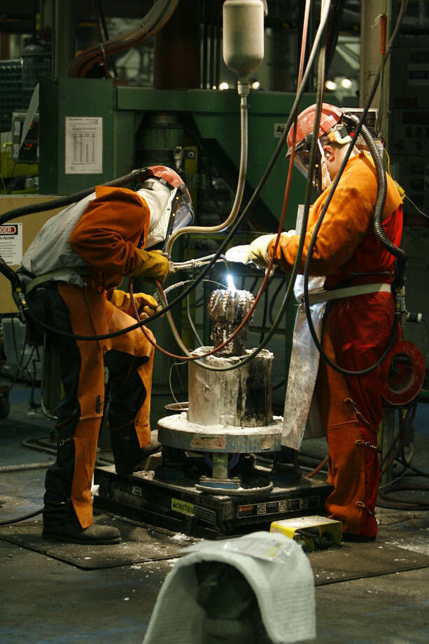 Lynn Franklin (left) brazing a PDC (polycrystalline diamond compact) bit as Byron Smith (right) applies flux, as they work at Halliburton's Security Drill Bits in 2007 in Conroe. Photo: Melissa Phillip, Houston Chronicle