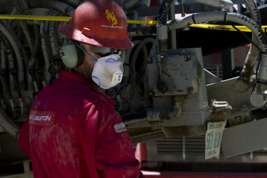 "A worker with Halliburton works on a well pad just after a charge was released in a well thousands of feet below creating multiple fractures in the cement-like crust that releases the ""tight gas"" in the Piceance Basin on the western slope of the Rocky Mountains in 2009. Photo: Johnny Hanson, Houston Chronicle"