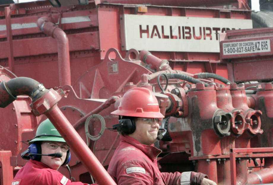 Halliburton workers are shown at a natural gas drilling site near Ponder, Texas, Friday, Jan. 3, 2006. The oilfield services conglomerate said Thursday that first-quarter net income rose 33 percent, a boost driven largely by increased sales and robust rig activity in North America. Photo: Donna McWilliam, AP