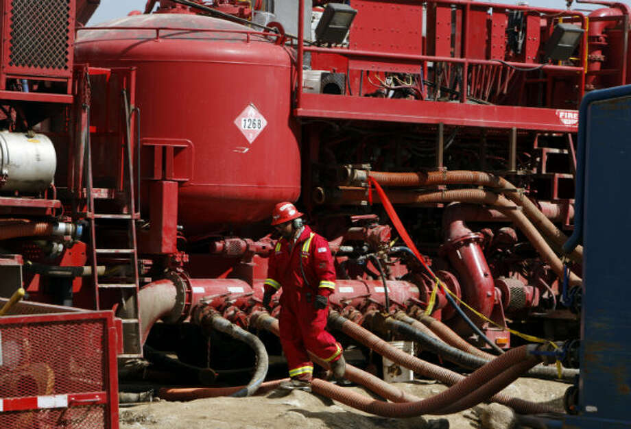 An unidentified worker steps through the maze of hoses being used at a remote fracking site being run by Halliburton for natural-gas producer Williams in Rulison, Colo. Photo: David Zalubowski, AP