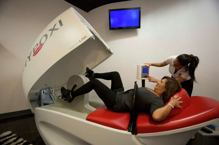 Hypoxi Houston co-owner Mireya Marache demonstrates one of the program's exercise devices with the help of her daughter, co-owner Caroline Goonie. Below, a monitor helps users stay within the fat-burning zone as they work out. Photo: Eric Kayne / © 2013 Eric Kayne