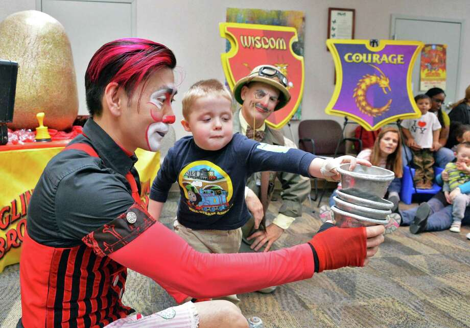 Four-year-old Christian Rittner of Guilderland assists clowns Rob Lok, left, and Joel Jeske of Ringling Bros. and Barnum & Bailey Circus as they perform Science of the Circus for 150 elementary school children at CloverPatch Elementary School at the Center for Disability Services in Albany, NY Tuesday April 23, 2013.  (John Carl D'Annibale / Times Union) Photo: John Carl D'Annibale / 10022086A