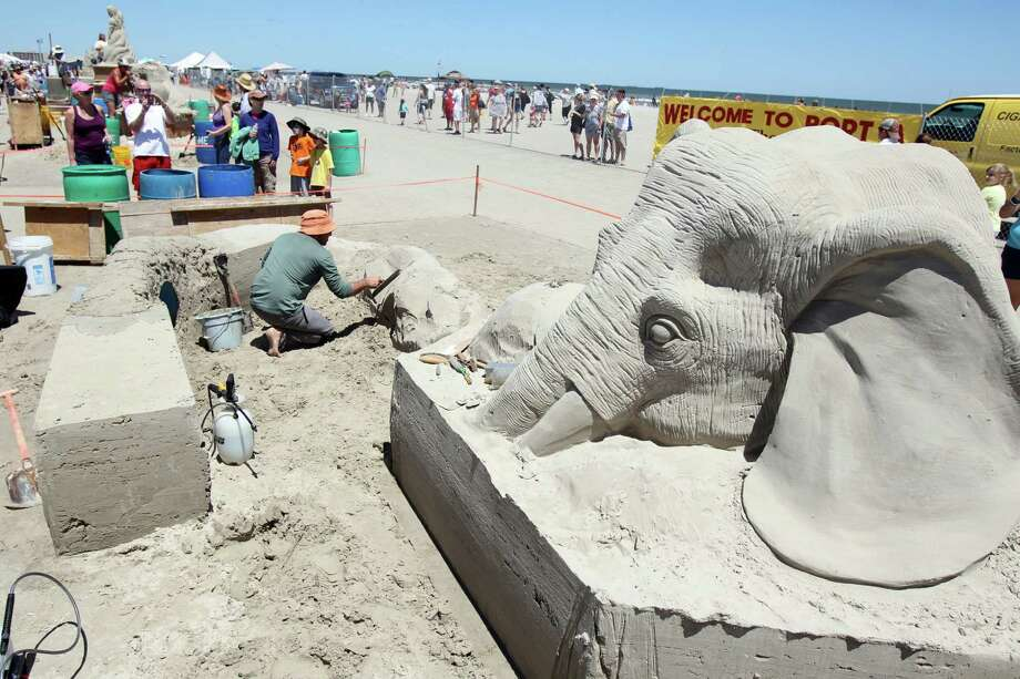 Wilfred Stiljger of the Netherlands, left, molds the elephant trunk Saturday, April 21, 2012 as he and sculpting partner Edith van de Wetering work on their creation during Texas Sandfest in Port Aransas, Texas. Master sand sculptors began working on their creations Friday evening. Their completed works will be on display today(Sunday) for the final day of the festival. (AP Photo/Corpus Christi Caller-Times, Michael Zamora) TV OUT; MAGS OUT Photo: Michael Zamora, Associated Press / AP2012