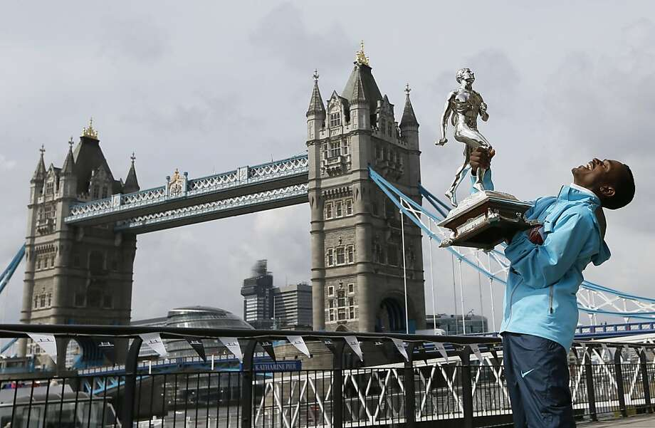 Laugh maniacally for the camera, please:London Marathon winner Tsegaye Kebede of Ethiopia finds posing with his trophy in front of the Tower Bridge hilarious. Photo: Kirsty Wigglesworth, Associated Press