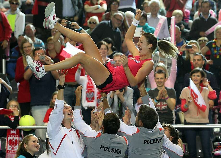 Pole vault:Polish team members celebrate as they launch Urszula Radwanska into the air after beating Belgium on the second day of the Fed Cup tennis World Group II Play-off match in Koksijde, Belgium. Photo: Yves Logghe, Associated Press