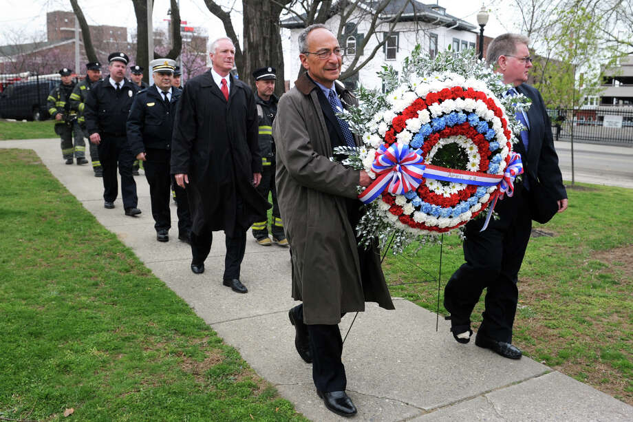 Former Mayor Thomas Bucci, left, and Peter Carroll carry a wreath to be placed at the L'Ambiance Plaza Memorial during a ceremony marking the 26th anniversary of the deadly collpase, in Bridgeport, Conn., April 23rd, 2013. 28 workers were killed in the 1987 construction accident. Photo: Ned Gerard / Connecticut Post
