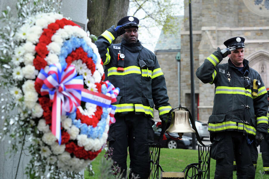 Bridgeport firefigher Christopher Robinson, left, rings a bell as each of the names of those killed in the L'Ambiance Plaza collapse are read during a ceremony marking the 26th anniversary of the accident, in Bridgeport, Conn., April 23rd, 2013. 28 workers were killed in the 1987 collapse. Robinson is seen here with fellow firefighter Jacob Hall. Photo: Ned Gerard / Connecticut Post