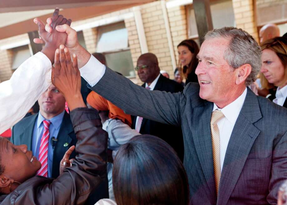 FILE - In this July 5, 2012 file photo provided by the George W. Bush Presidential Center, former President George W. Bush and his wife, Laura Bush stop to talk with people who have lined the hallways of the Princess Marina Hospital in Gaborone, Botswana. The government spent nearly $3.7 million on former presidents in 2012, according to an analysis just released by the nonpartisan Congressional Research Service. That covers a pension, compensation and benefits for office staff, and other costs like travel, office space and postage. The costliest former president? George W. Bush, who clocked in last year at just over $1.3 million. (AP Photo/George W. Bush Presidential Center, Shealah Craighead, File) Photo: Shealah Craighead, Associated Press / George W. Bush Presidential Cent