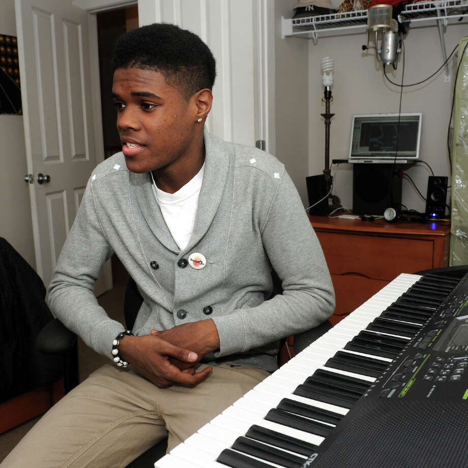 Demetri Smith, a senior at Bassick High School, sits at his piano in his Bridgeport, Conn. home, April 19th, 2013. Smith has been awarded a full scholarship to the University of New Haven. Photo: Ned Gerard / Connecticut Post