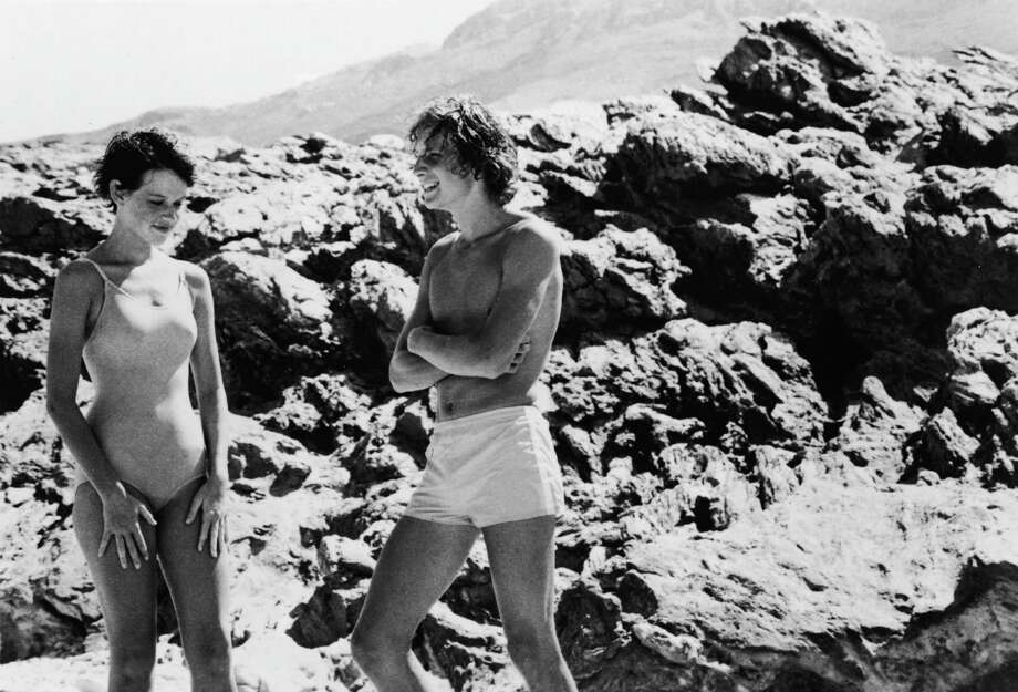 American actors Molly Ringwald and Sam Robards, both in swimming suits, talk together on a rocky beach in a scene from 'Tempest,' directed by Paul Mazursky, 1982. The film is based on William Shakespeare's play and was Ringwald's big-screen debut. Photo: Columbia TriStar, Getty / Moviepix