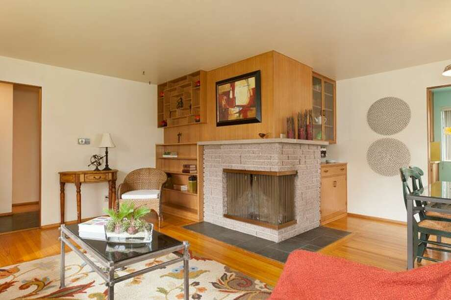 Living and dining rooms of 10522 Evanston Ave. N. The 1,960-square-foot house, built in 1956, has three bedrooms, one bathroom, two fireplaces, a rec room and built-ins on a 6,300-square-foot lot. It's listed for $339,500, although a sale is pending. Photo: Courtesy Roberta Pletz, Windermere Real Estate