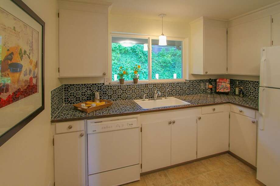 Kitchen of 13514 North Park Ave. N. The 1,490-square-foot home, built in 1955, has three bedrooms, two bathrooms, a slate entry, two fireplaces, a family room, exposed wood doors and moldings, French doors and a patio on a 5,929-square-foot lot with lakefront rights to a small private park. It's listed for $350,000, although a sale is pending. Photo: TCPeterson Photography, Courtesy Eva Brandenburg, Lake & Co. Real Estate