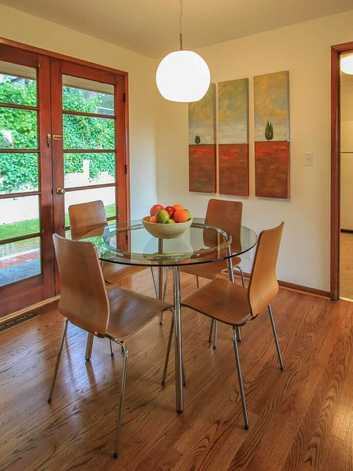 Dining room of 13514 North Park Ave. N. The 1,490-square-foot home, built in 1955, has three bedrooms, two bathrooms, a slate entry, two fireplaces, a family room, exposed wood doors and moldings, French doors and a patio on a 5,929-square-foot lot with lakefront rights to a small private park. It's listed for $350,000, although a sale is pending. Photo: TCPeterson Photography, Courtesy Eva Brandenburg, Lake & Co. Real Estate