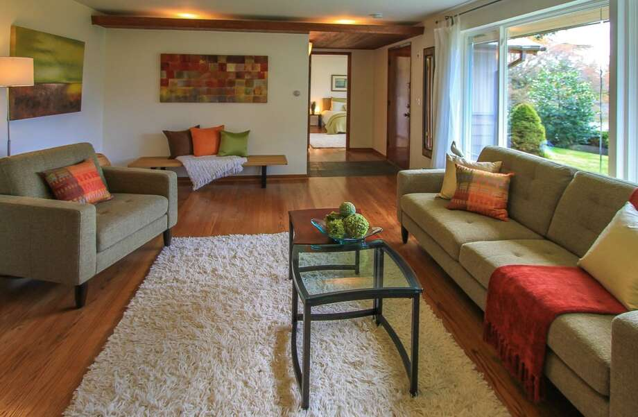 Living room of 13514 North Park Ave. N. The 1,490-square-foot home, built in 1955, has three bedrooms, two bathrooms, a slate entry, two fireplaces, a family room, exposed wood doors and moldings, French doors and a patio on a 5,929-square-foot lot with lakefront rights to a small private park. It's listed for $350,000, although a sale is pending. Photo: TCPeterson Photography, Courtesy Eva Brandenburg, Lake & Co. Real Estate
