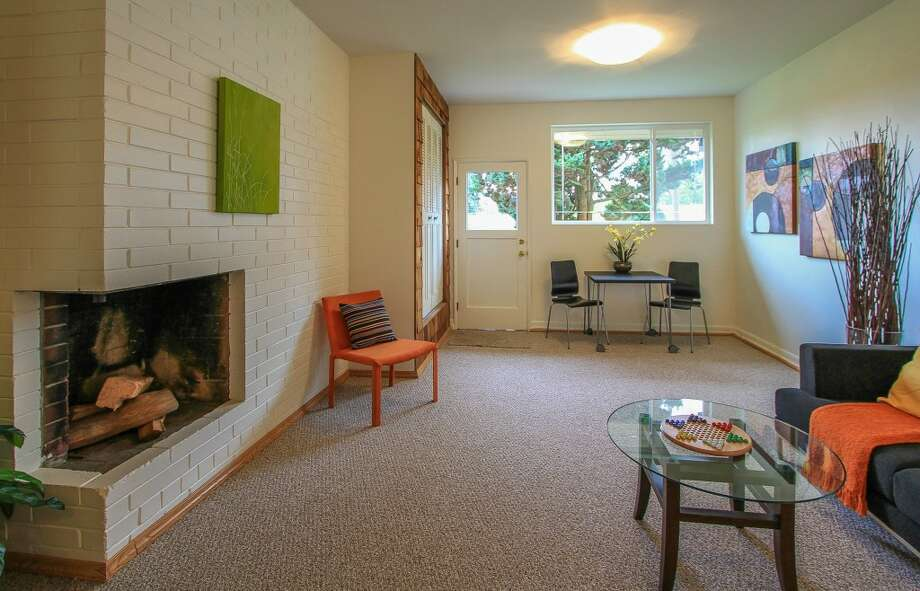 Family room of 13514 North Park Ave. N. The 1,490-square-foot home, built in 1955, has three bedrooms, two bathrooms, a slate entry, two fireplaces, a family room, exposed wood doors and moldings, French doors and a patio on a 5,929-square-foot lot with lakefront rights to a small private park. It's listed for $350,000, although a sale is pending. Photo: TCPeterson Photography, Courtesy Eva Brandenburg, Lake & Co. Real Estate