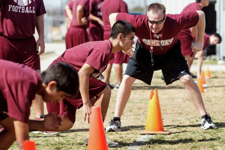 Marshall football coach Tim Williams (right) works on agility drills with the team at the school earlier this year. Williams had previously coached at Holmes for the past four years.
