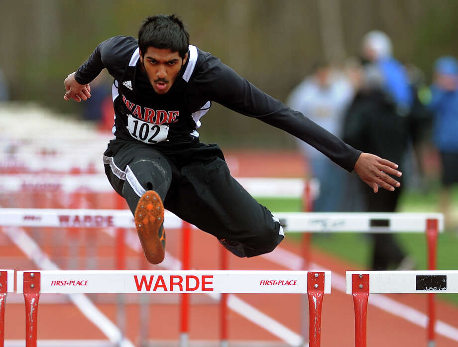 Fairfield Warde's Narender Arjoon clears a hurdle, during track meet action against Trumbull and Danbury in Fairfield, Conn. on Tuesday April 23, 2013. Photo: Christian Abraham / Connecticut Post