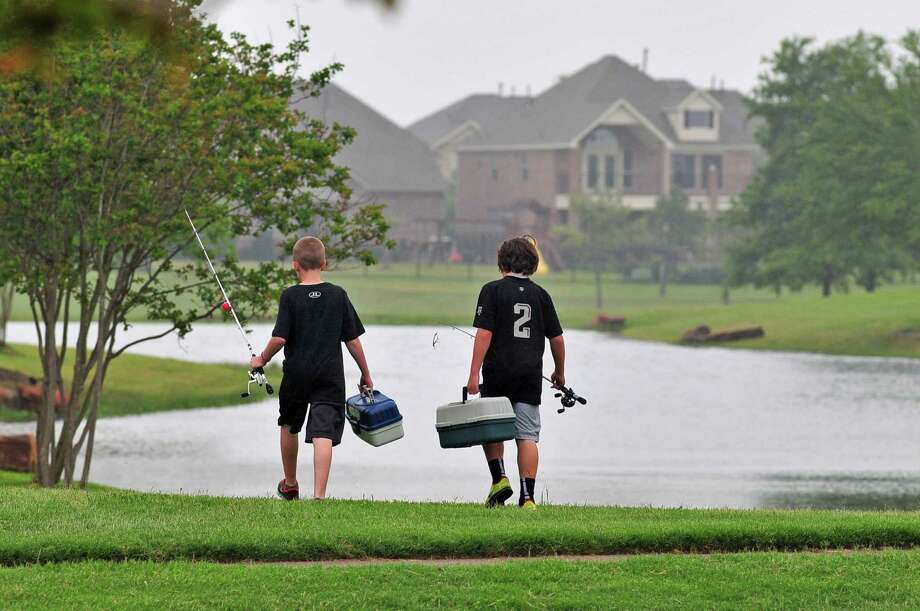Cade Lippincott, 11, and Jaryn Sims, 10, carry their gear to their favorite fishing spot in the Bridgeland community. The 11,400-acre master-planned community off Fry Road has a variety of activities for children. Photo: Â Tony Bullard 2013, Freelance Photographer / © Tony Bullard & the Houston Chronicle