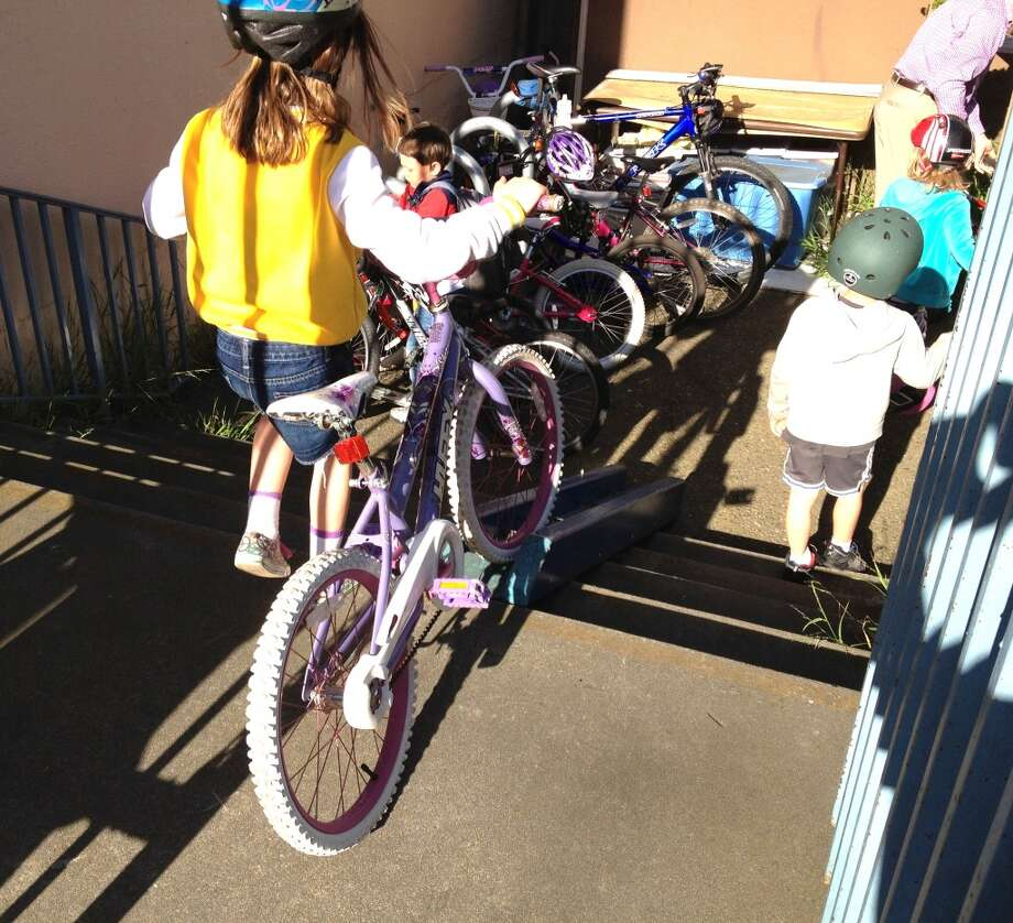 Sophia uses the helpful ramp to get her bike down the stairs.