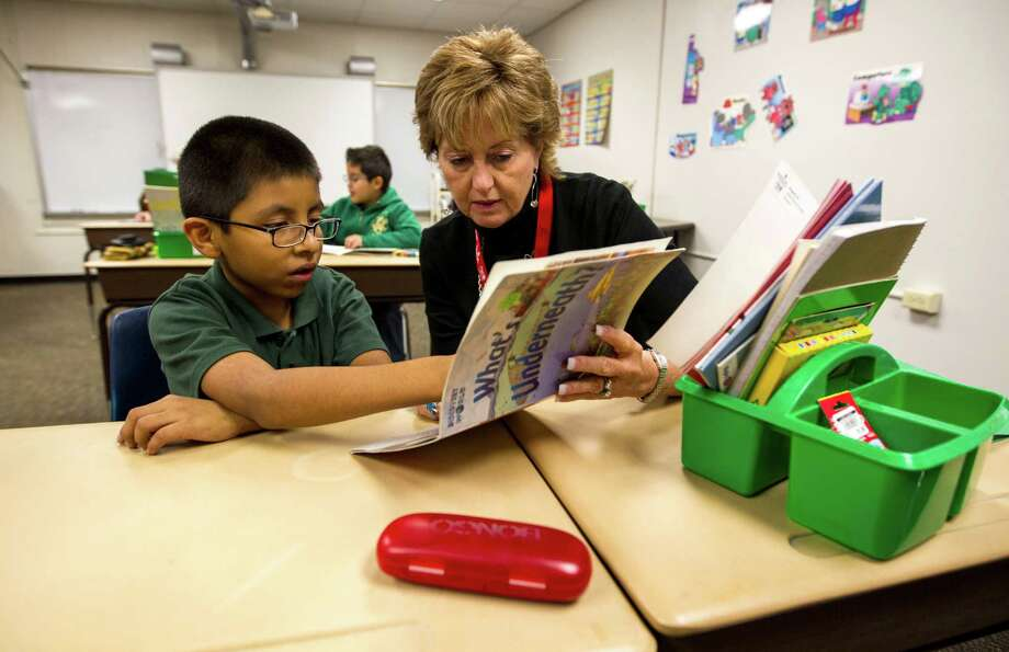 Volunteer Linda Aldrich helps second-grader Gustavo Segura read during the United Way's Reading Together initiative in January at Spring Shadows Elementary School. Photo: Karen Warren, Staff / 2013 Houston Chronicle