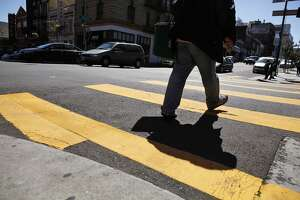 A pedestrian makes his way through the crosswalk at the intersection of Polk Street and Bush Streets in San Francisco, Calif., on Tuesday, April 23, 2013. The Walk About Town column is about a project to improve Polk Street's walkability, where shoppers and pedestrians could get better safety in intersections and on the crowded sidewalks on Polk Street near Geary and Pine Streets.