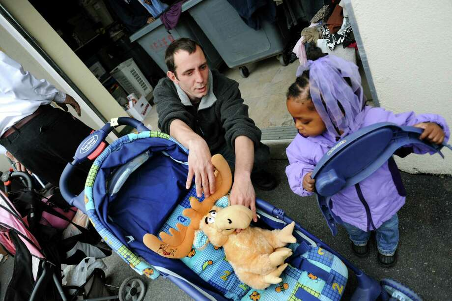 Volunteer Jason Scutt, left, places a stuffed moose in the baby carriage of Nia Holmes, 2, of Albany on Tuesday, April 23, 2013, at Blessingdale's thrift shop in Albany, N.Y. Scutt was trying to appease the child who wanted a baby doll. (Cindy Schultz / Times Union) Photo: Cindy Schultz / 00022050A