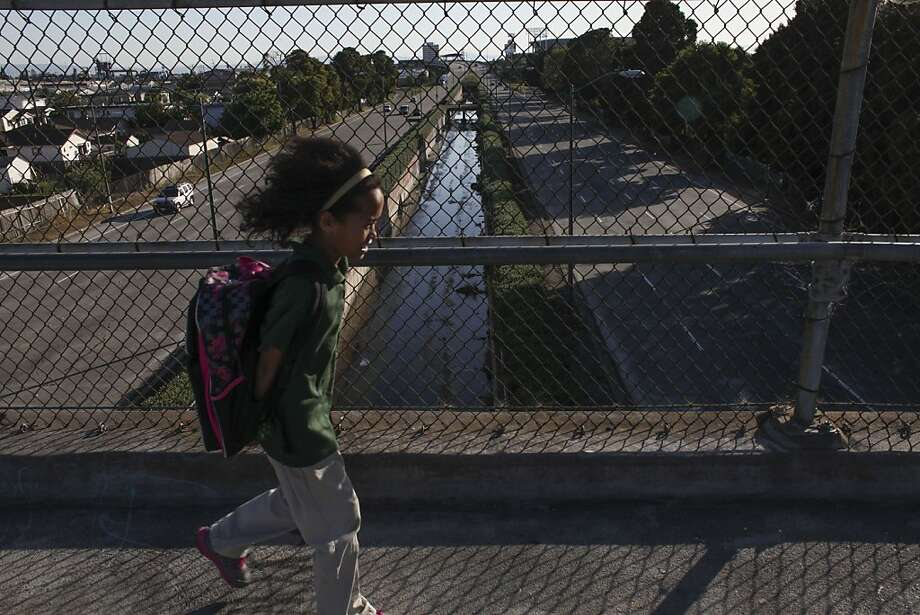 Serenity Davis, backpack and all, powers across an overpass near Hegenberger Road in Oakland, which is included in the list of the 10 most polluted ZIP codes in California known as CalEnviroScreen. Photo: Sam Wolson, Special To The Chronicle
