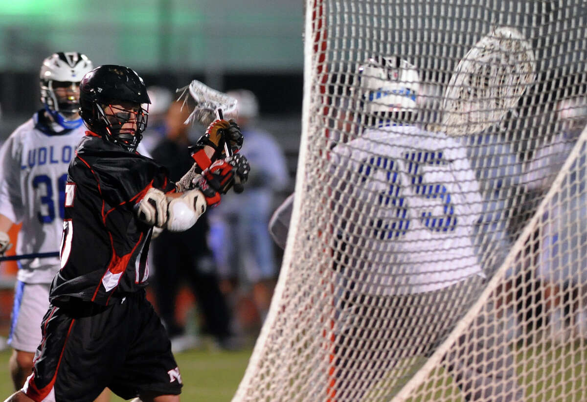 New Canaan's Henry Stanton prepares to send a shot past Fairfield Ludlowe goalie Thomas Kryspin for a goal, during boys lacrosse action in Fairfield, Conn. on Tuesday April 23, 2013.