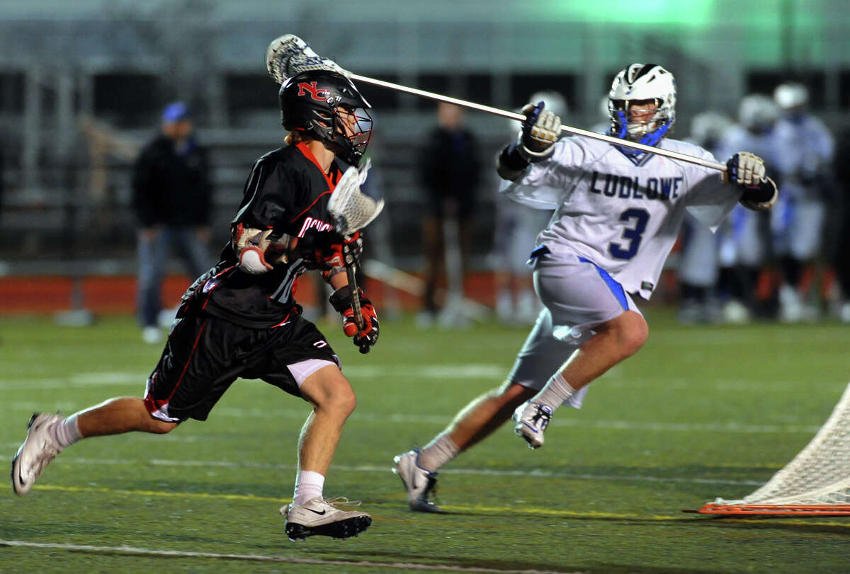 New Canaan's Peter Richardson drives the ball past Fairfield Ludlowe's Justin Knowles, during boys lacrosse action in Fairfield, Conn. on Tuesday April 23, 2013.