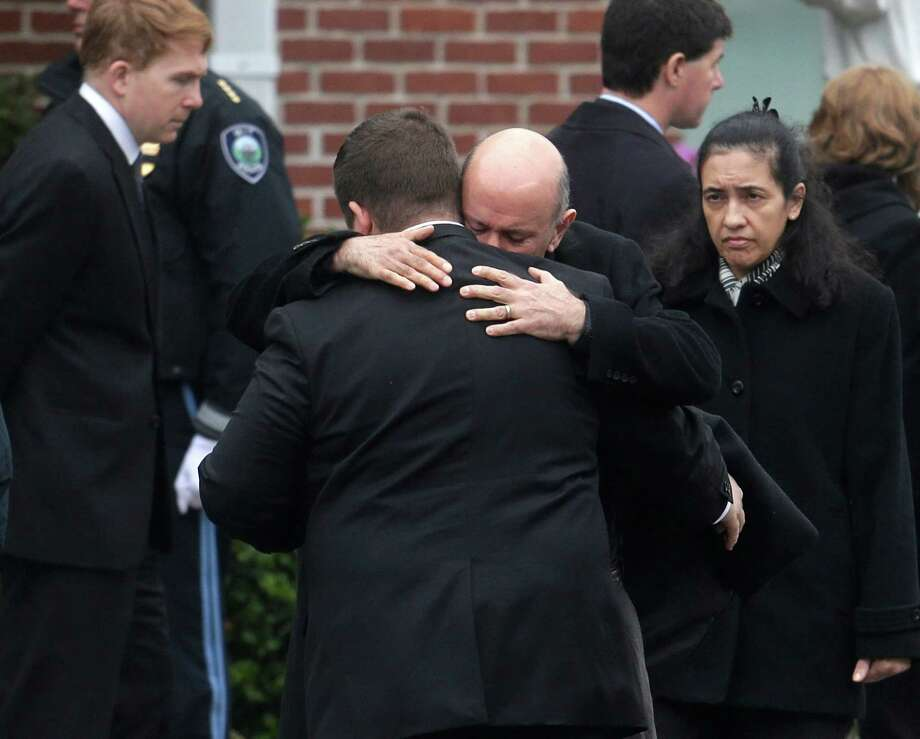 Mourners hug as they depart St. Patrick's Church in Stoneham, Mass., following a funeral Mass for Massachusetts Institute of Technology police officer Sean Collier, Tuesday, April 23, 2013. Collier was fatally shot on the MIT campus Thursday, April 18, 2013. Authorities allege that the Boston Marathon bombing suspects were responsible. (AP Photo/Steven Senne) Photo: Steven Senne