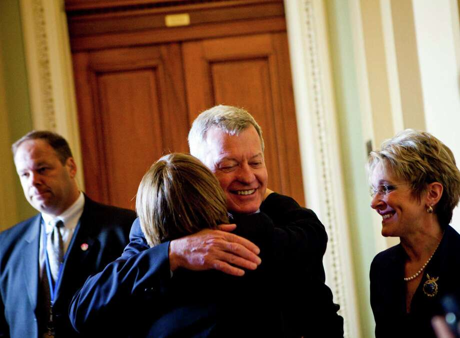 Sen. Max Baucus (D-Mont.) receives a hug from Sen. Amy Klobuchar (D-Minn.) on Capitol Hill, in Washington, April 23, 2013. Baucus, the chairman of the Finance Committee, will retire from the Senate after 36 years, the sixth Senate Democrat to head to the exits in 2014, Democratic officials said on April 23. (Christopher Gregory/The New York Times) Photo: CHRISTOPHER GREGORY / NYTNS