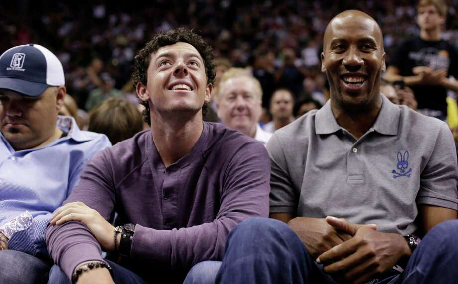 Golfer Rory McIlroy, left, and former San Antonio Spurs forward Bruce Bowen, right, attend a Spurs game against Miami on Sunday in San Antonio. McIlroy is schedule to play in the Texas Open golf tournament in San Antonio this week. Photo: Eric Gay, Photo By Eric Gay | AP / AP