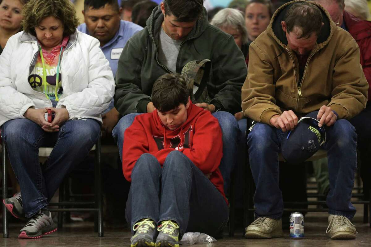 West residents Kathy Gremminger, left, Nick Nors, center, James Lenart, right, and Christy Nors, on floor, Nick's wife, bow their heads in prayer at the start of a town hall meeting held at the Knights of Columbus Hall for residents of West, TX, affected by the recent blast, on Tuesday April 23, 2013.