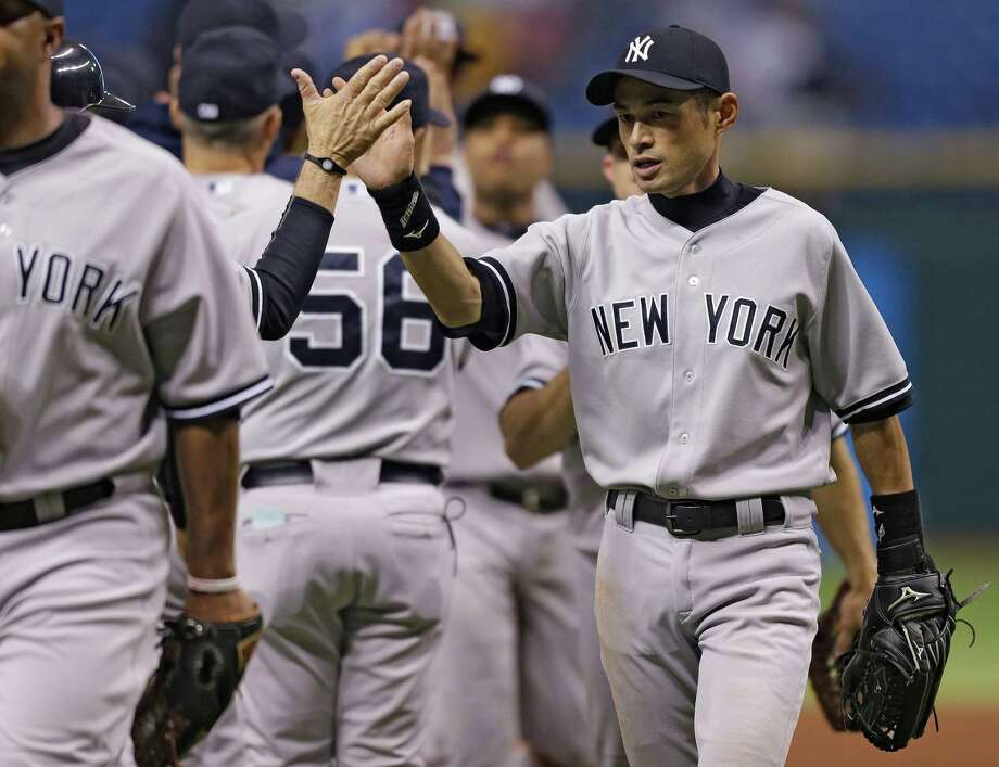 New York Yankees' Ichiro Suzuki, of Japan, right, high fives teammates after the Yankees defeated the Tampa Bay Rays 4-3 during a baseball game Tuesday, April 23, 2013, in St. Petersburg, Fla. Suzuki hit a two-run single off Tampa Bay Rays relief pitcher Fernando Rodney. (AP Photo/Chris O'Meara) Photo: Chris O'Meara