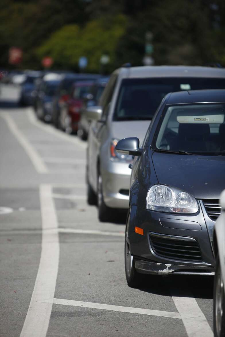 Some cars are seen parked on top of a striped buffer zone next to the bike lane along John F. Kennedy Drive in Golden Gate Park on Tuesday, April 23 2013 in San Francisco, Calif.