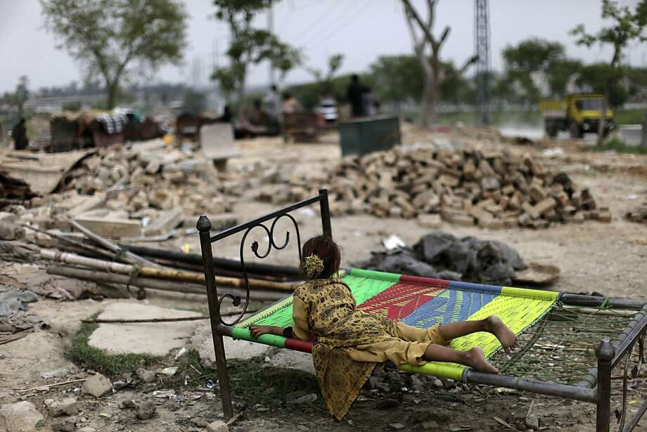 A Pakistani girl, who was displaced with her family by 2010 floods in Pakistan's Sindh province, lies on a bed next to the rubble of her makeshift home, after it was destroyed along with other homes by the Capital Development Authority for being built on illegal lands, on the outskirts of Islamabad, Pakistan, Tuesday, April 23, 2013. Many slums which are built on illegal lands have neither running water or sewage disposal. (AP Photo/Muhammed Muheisen) Photo: Muhammed Muheisen, Associated Press