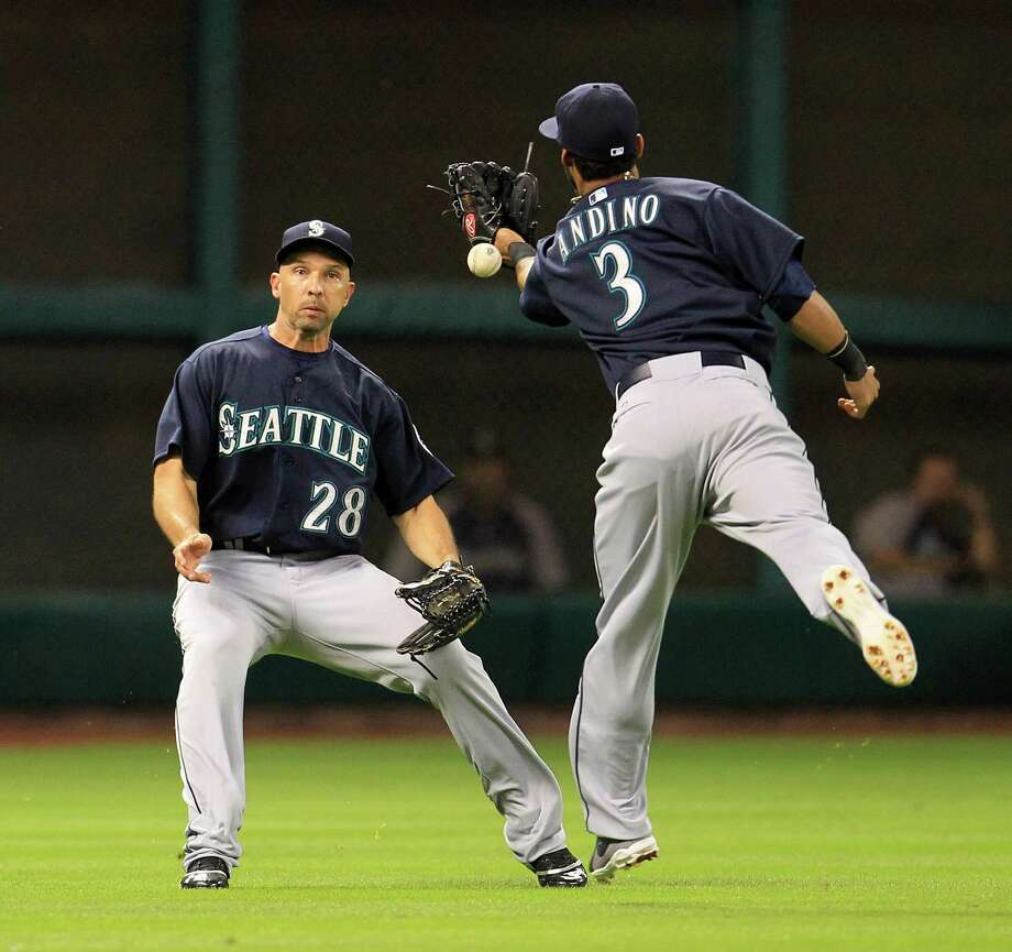Mariners shortstop Robert Andino drops a popup hit by Marwin Gonzalez as left fielder Raul Ibanez approaches in the eighth inning Tuesday night. Photo: Karen Warren, Staff / © 2013 Houston Chronicle