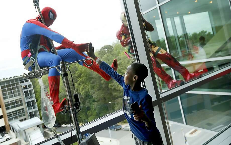 "Jacob Smith 10, greets Spider-Man, who is played by Marcos Medrano, through the window as window washers from Scottie's Building Services drop in to greet patients of WakeMed's Children's Hospital Tuesday, April 23, 2013. Spider-Man, Batman and Iron Man spent the day outside the windows of the lobby and children's rooms.  ""It's awesome"" said Smith, who has been in the hospital two nights, of the superhero visit. (Ethan Hyman/Raleigh News & Observer/MCT) Photo: Ethan Hyman, McClatchy-Tribune News Service"