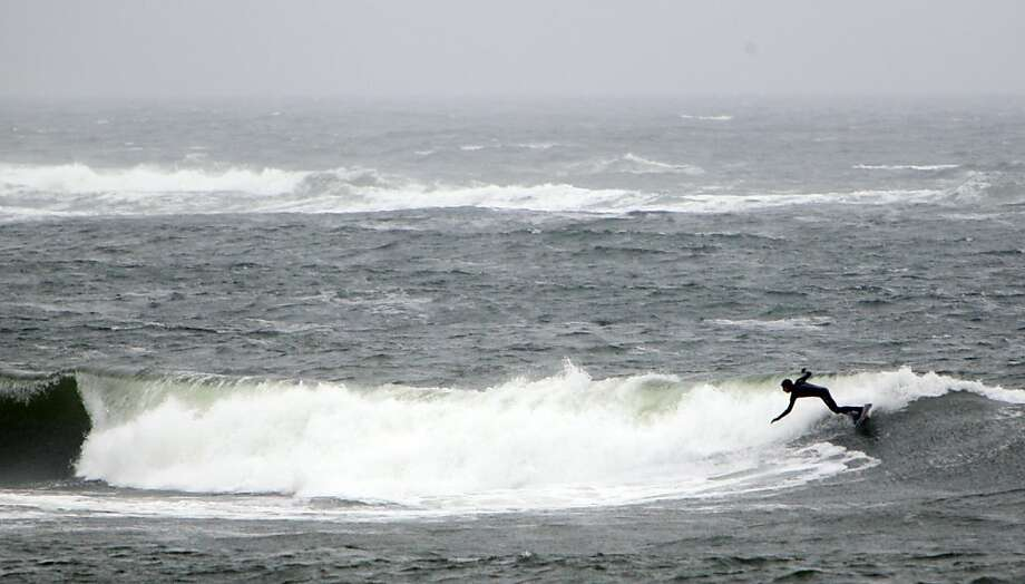 A surfer is seen in the rough waters on the New Hampshire coast, Tuesday, April 23, 2013, off Hampton, N.H. (AP Photo/Jim Cole) Photo: Jim Cole, Associated Press