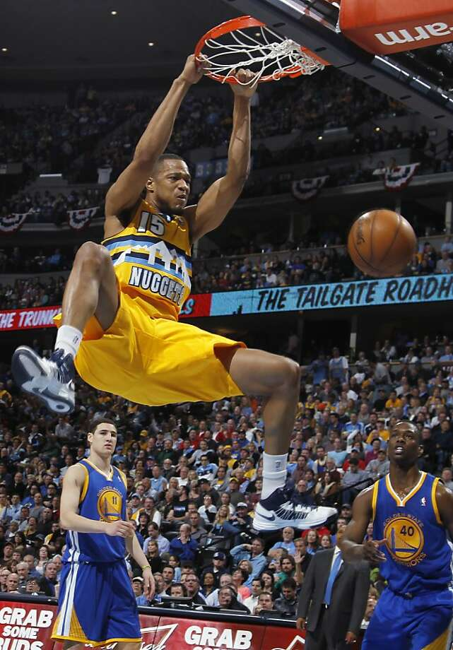 Denver Nuggets forward Anthony Randolph, front, hangs from the rim after dunking the ball for a basket as Golden State Warriors guard Klay Thompson, back left, and forward Harrison Barnes look on in the fourth quarter of the Warriors' 131-117 victory in Game 2 of the teams' NBA first-round playoff series in Denver on Tuesday, April 23, 2013. (AP Photo/David Zalubowski) Photo: David Zalubowski, Associated Press