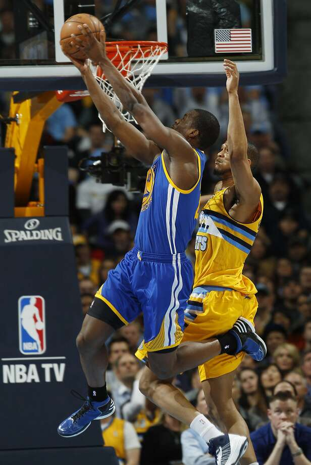 Golden State Warriors forward Harrison Barnes, front, goes up for a reverse dunk past Denver Nuggets forward Anthony Randolph in the fourth quarter of the Warriors' 131-117 victory in Game 2 of the teams' NBA first-round playoff series in Denver on Tuesday, April 23, 2013. (AP Photo/David Zalubowski) Photo: David Zalubowski, Associated Press