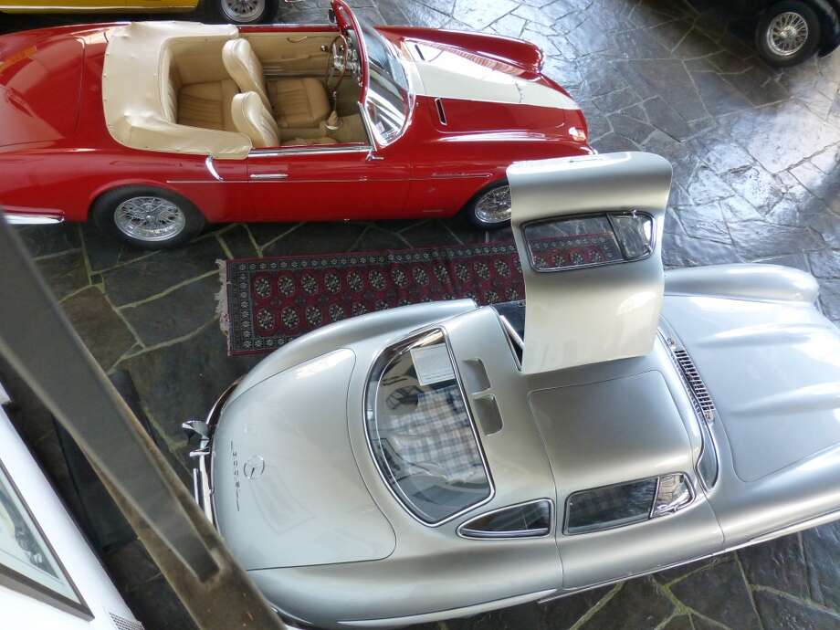A silver Mercedes-Benz gullwing and a red Maserati roadster. .