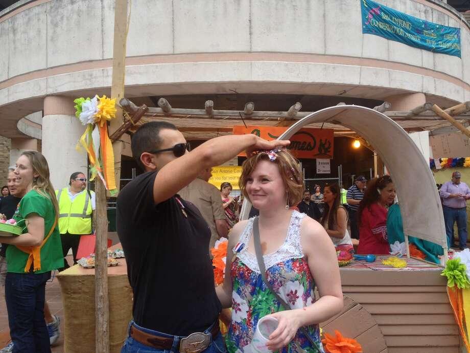 Justin Alvarado cracks a cascaron over Shawna Robinson's head at NIOSA Tuesday. Photo: Sarah Tressler/Express-News