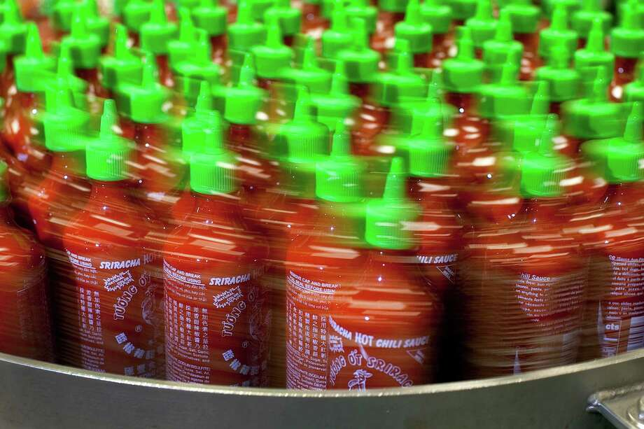 Bottles of Sriracha Hot Chili Sauce move through a conveyor belt ready for packaging at Huy Fong Foods in Rosemead, California. The company is moving to a nearby facility that could triple its production capacity. (Gina Ferazzi/Los Angeles Times/MCT) Photo: Gina Ferazzi / Los Angeles Times